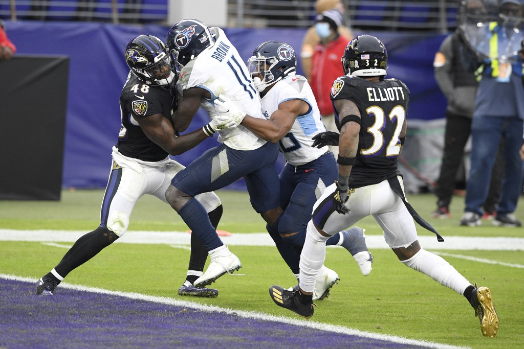 Tennessee Titans wide receiver A.J. Brown (11) gets help from teammate running back Jeremy McNichols, center right, while scoring against Baltimore Ra...