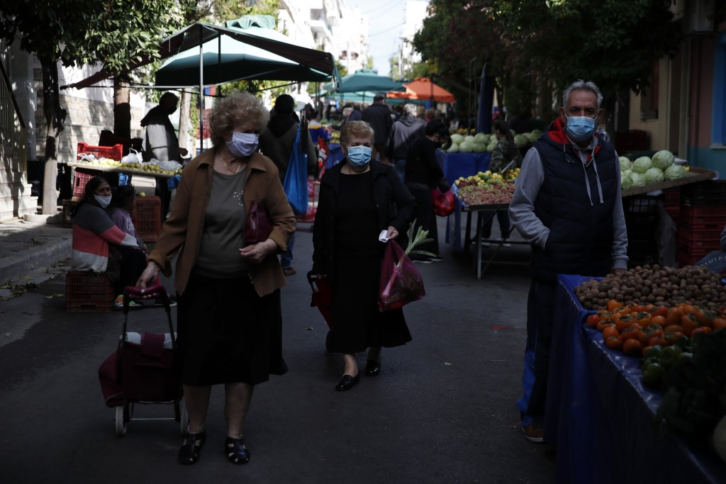 Two women wearing face masks against the spread of coronavirus, pull their trolley baskets at an open-air fruit and vegetable market in Athens, Monday...