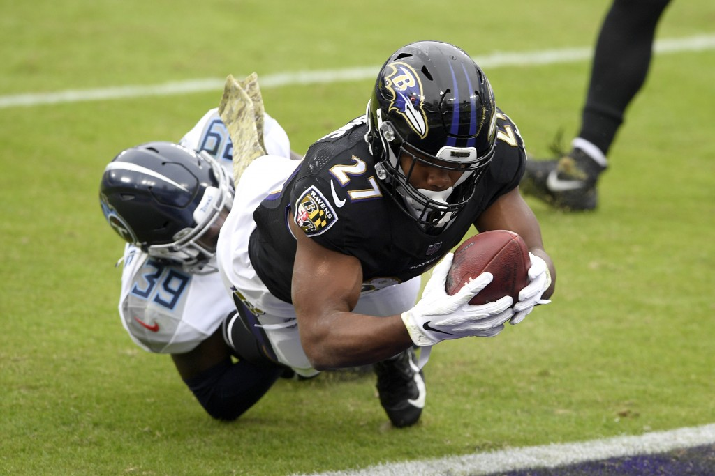 Baltimore Ravens running back J.K. Dobbins (27) dives into the end zone as Tennessee Titans cornerback Breon Borders tries to stop him on a 2-point co...