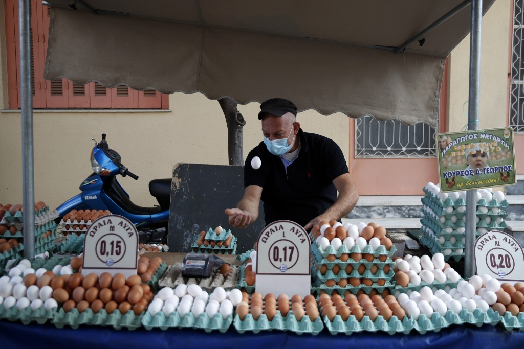 A vendor wearing a face mask against the spread of coronavirus, throws and catches an egg in the air at an open-air fruit and vegetable market in Athe...