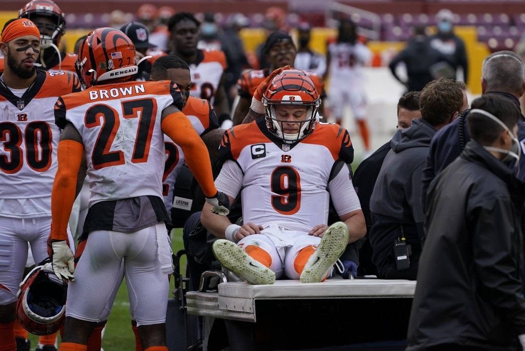 Cincinnati Bengals quarterback Joe Burrow (9) is consoled by teammates as he is carted off the field during the second half of an NFL football game ag...