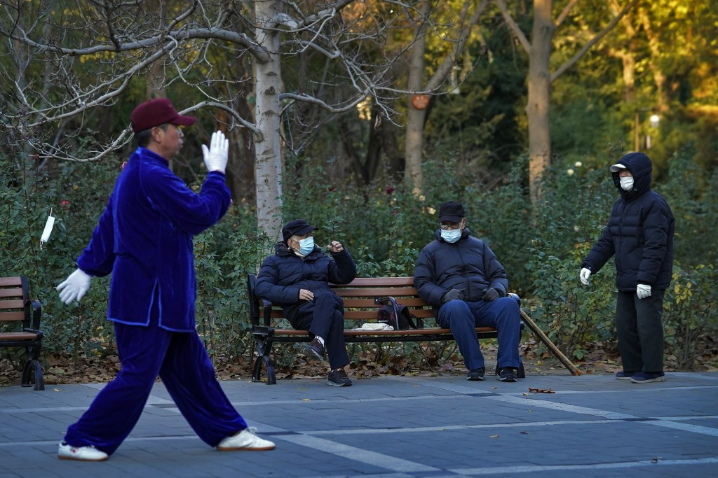 People wearing face masks to help curb the spread of the coronavirus chat each other as a man performs morning exercise at a park in Beijing, Monday, ...