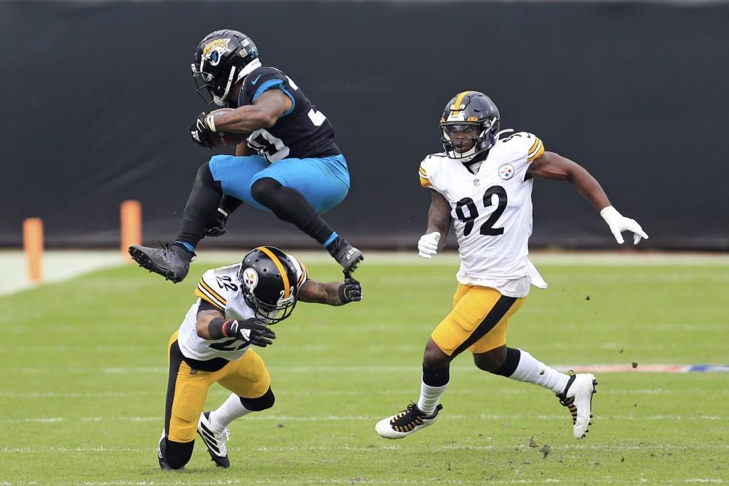 Jacksonville Jaguars running back James Robinson, left, leaps over Pittsburgh Steelers cornerback Steven Nelson (22) as linebacker Olasunkanmi Adeniyi...