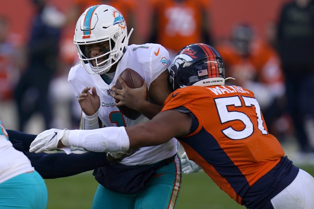 Miami Dolphins quarterback Tua Tagovailoa (1) is sacked by Denver Broncos defensive end DeMarcus Walker (57) during the first half of an NFL football ...