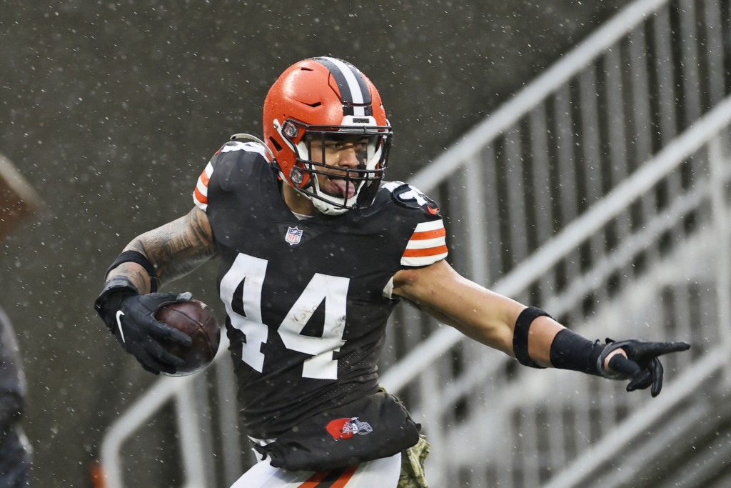 Cleveland Browns linebacker Sione Takitaki looks back as he runs for a 50-yard interception return touchdown during the first half of an NFL football ...