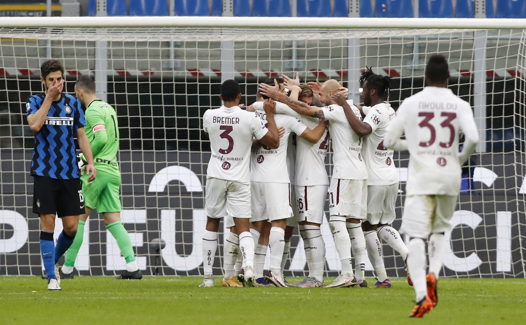 Torino's Cristian Ansaldi, covered by his teammates, celebrates after scoring his side's second goal during the Serie A soccer match between Inter Mil...