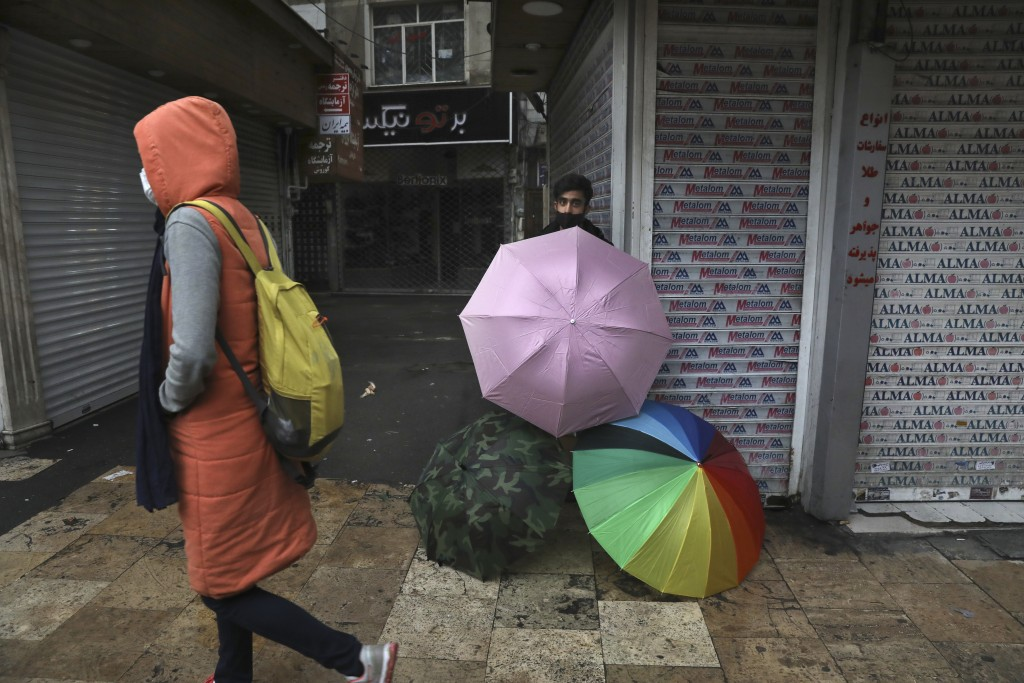 A vendor sells umbrellas outside closed shops in northern Tehran, Iran, Sunday, Nov. 22, 2020. Iran on Saturday shuttered businesses and curtailed tra...