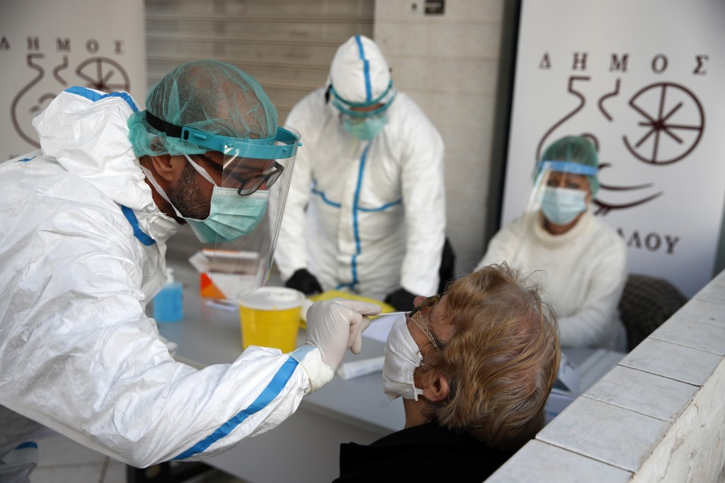 Medical staff conducts a rapid COVID test on an elderly woman in Athens, Monday, Nov. 23, 2020. Greece has seen a major resurgence of the virus after ...