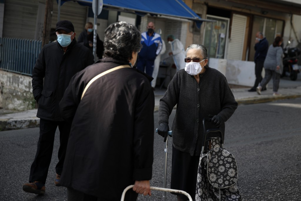 An elderly woman wearing a face mask against the spread of coronavirus, speaks with another woman, in Athens, Monday, Nov. 23, 2020. Greece has seen a...