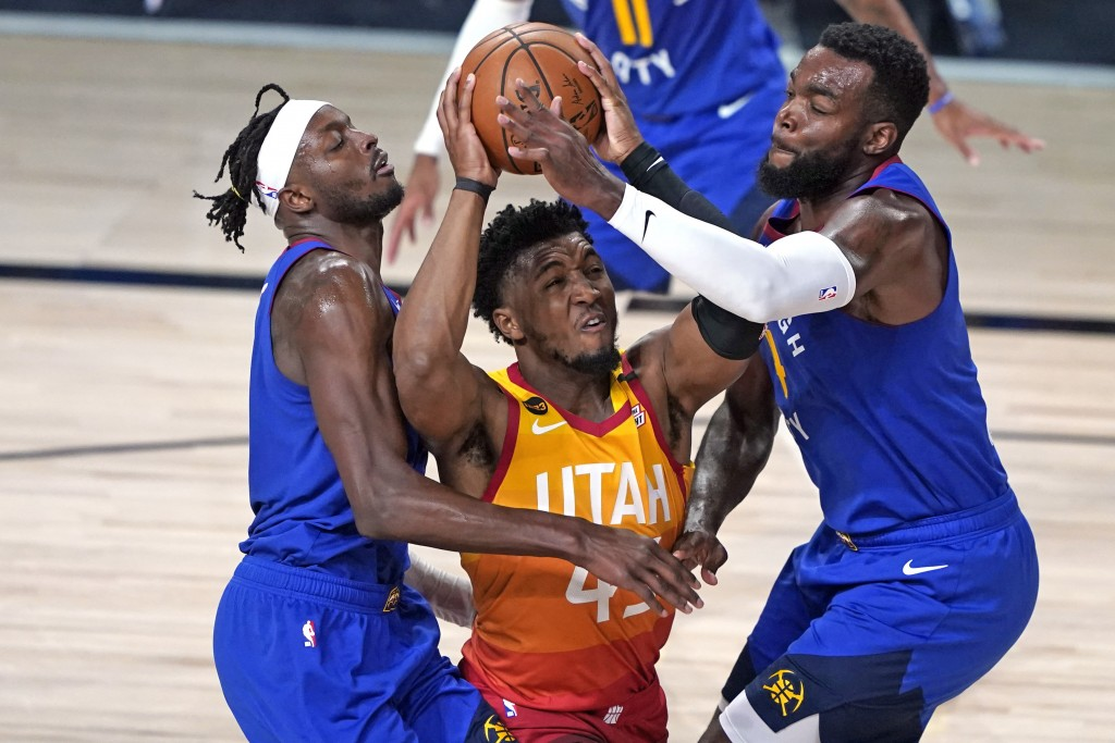 FILE - In this Aug. 30, 2020, file photo, Utah Jazz's Donovan Mitchell, center, goes up to shoot as Denver Nuggets' Jerami Grant, left, and Paul Mills...