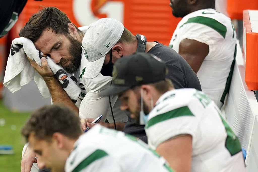 New York Jets quarterback Joe Flacco, top right, wipes sweat off his face during the second half of an NFL football game against the Los Angeles Charg...