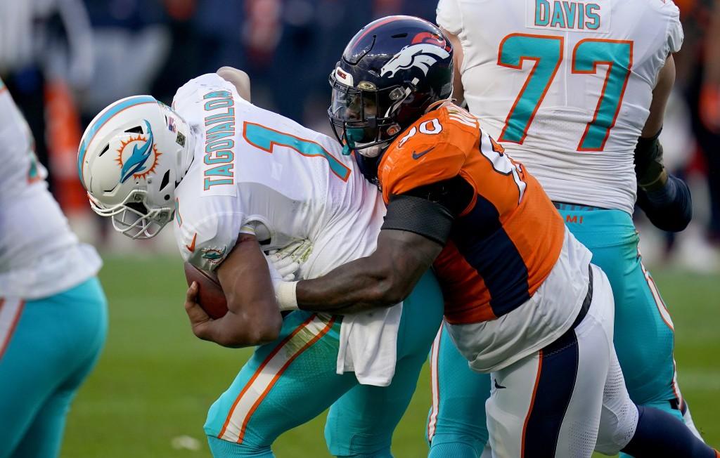 Denver Broncos defensive end DeShawn Williams (90) sacks Miami Dolphins quarterback Tua Tagovailoa (1) during the second half of an NFL football game,...
