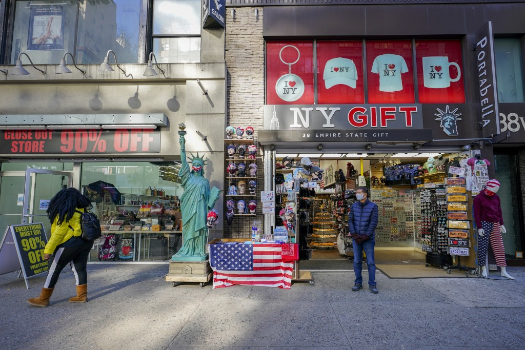 A shop keeper at a gift shop along 34th Street stands on the sidewalk waiting for customers, Friday, Nov. 20, 2020, in New York. In souvenir shops fro...