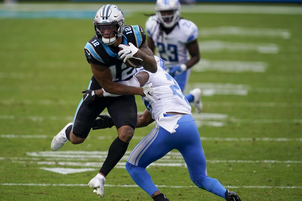 Carolina Panthers wide receiver D.J. Moore is tackled by Detroit Lions strong safety Duron Harmon during the second half of an NFL football game Sunda...