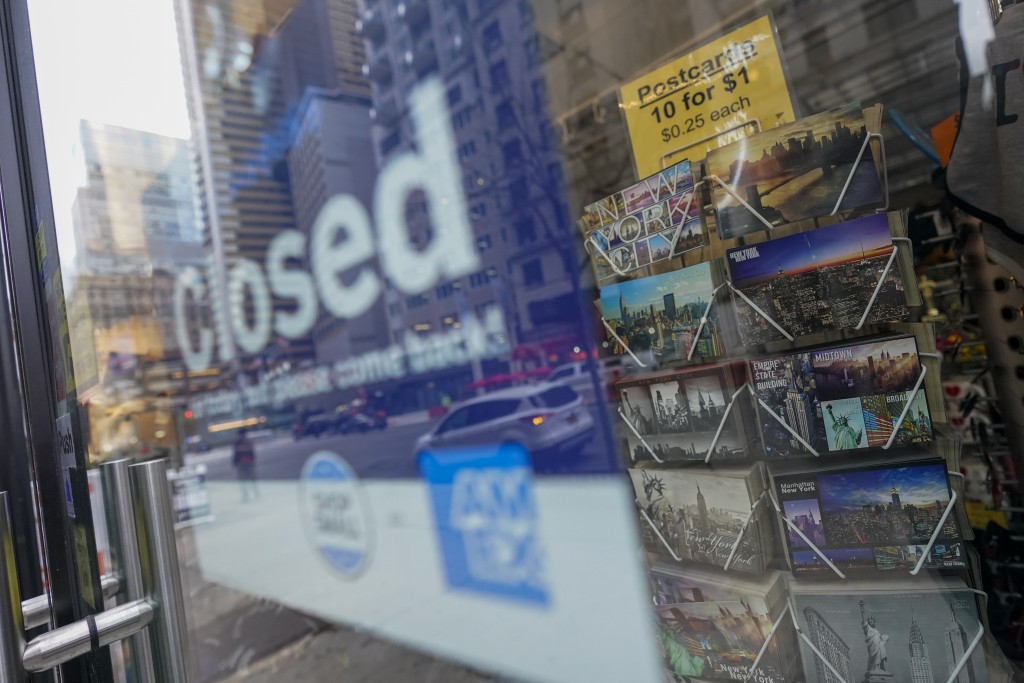 New York City postcards are seen on display for sale at a closed gift shop, Thursday, Nov. 12, 2020, in New York's Times Square. In souvenir shops fro...