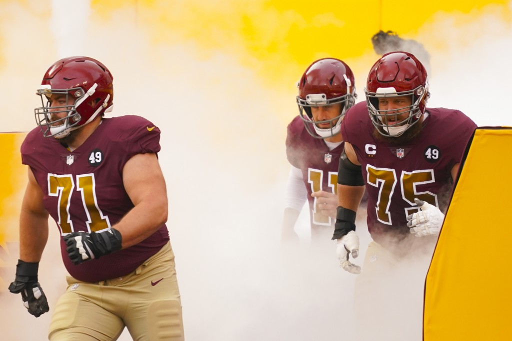 Members of the Washington Football Team taking the field, from l-r., offensive guard Wes Schweitzer (71), quarterback Alex Smith (11) and offensive gu...