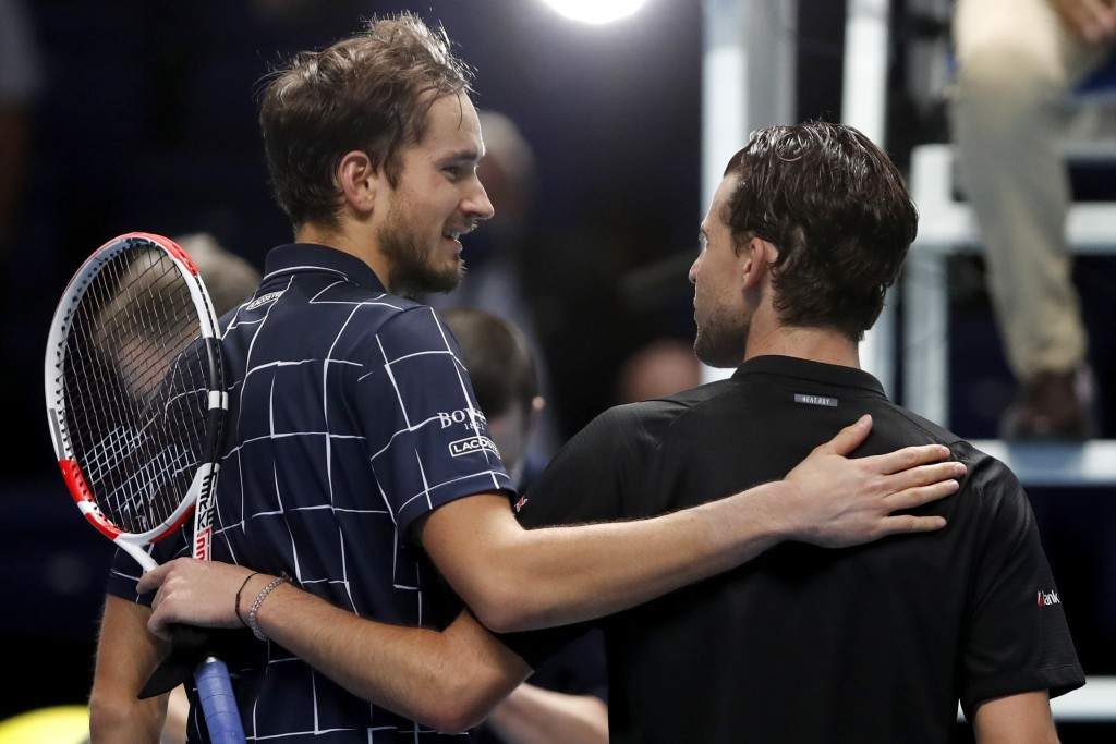 Daniil Medvedev of Russia, left, puts his arm around Dominic Thiem of Austria after he wins their singles final tennis match at the ATP World Finals t...