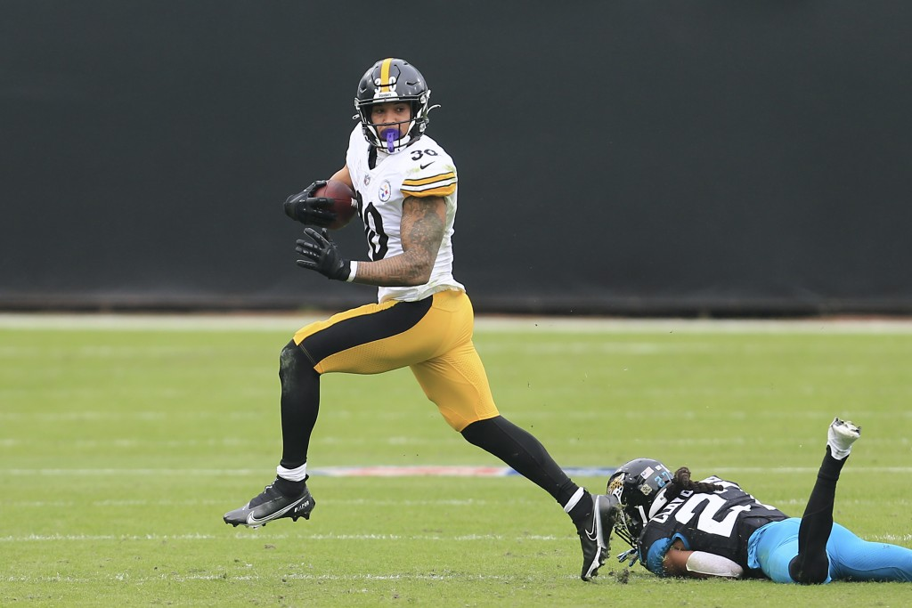 Pittsburgh Steelers running back James Conner, left, slips past Jacksonville Jaguars cornerback Chris Claybrooks for a gain during the first half of a...