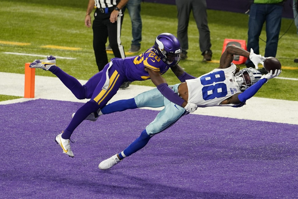 Dallas Cowboys wide receiver CeeDee Lamb (88) catches a 4-yard touchdown pass ahead of Minnesota Vikings cornerback Jeff Gladney, left, during the fir...