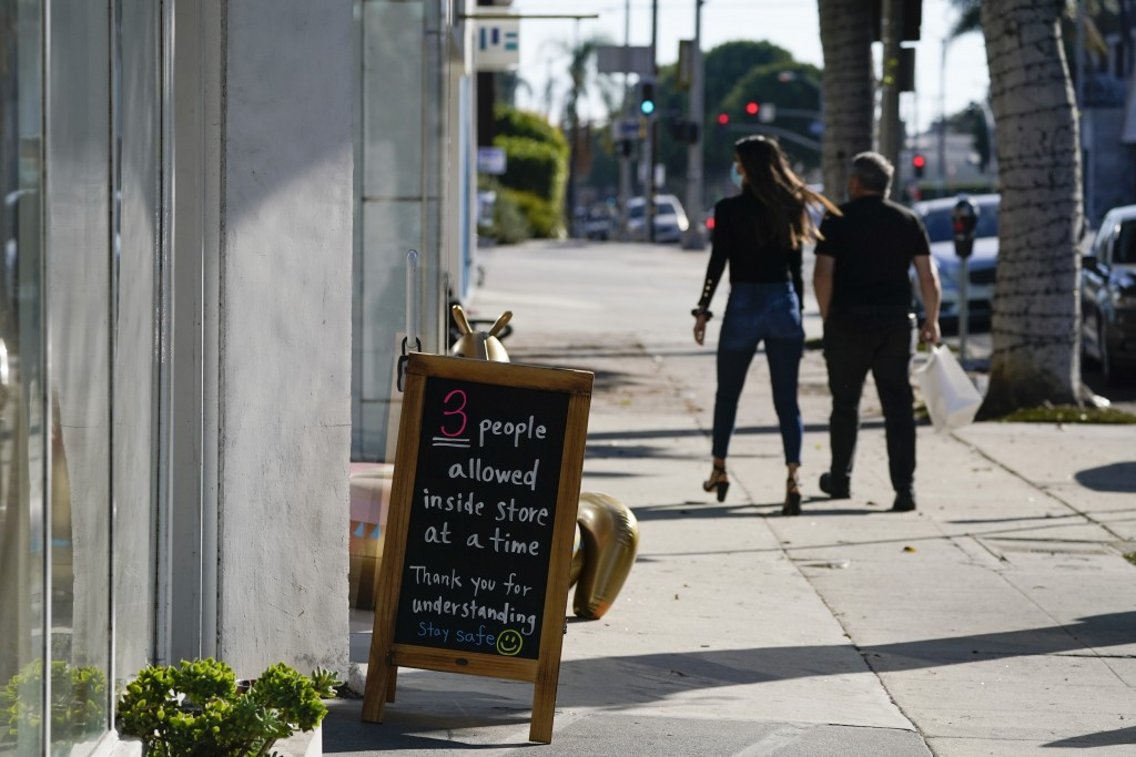 A sign restricting the number of customers stands outside of a shop Wednesday, Nov. 18, 2020, in West Hollywood, Calif. Los Angeles County imposed new...