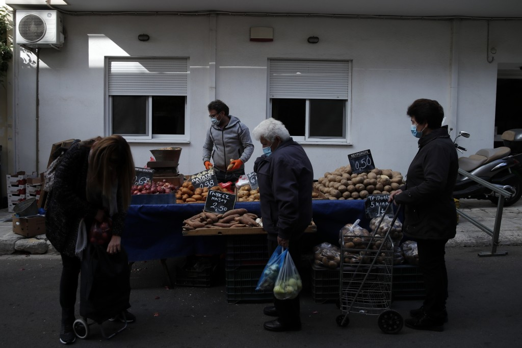 Customers wearing face masks against the spread of coronavirus, wait to buy potatoes at an open-air fruit and vegetable market in Athens, Monday, Nov....