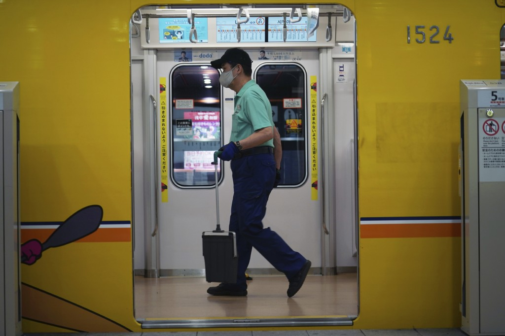 An employee wearing a protective mask to help curb the spread of the coronavirus cleans a subway car Tuesday, Nov. 24, 2020, in Tokyo. The Japanese ca...