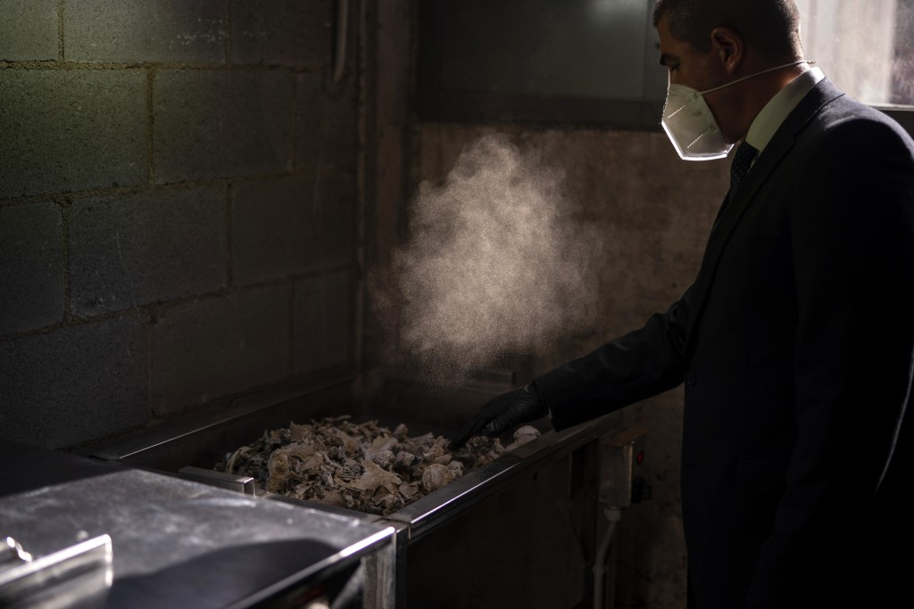 A mortuary worker collects the ashes of a COVID-19 victim from an oven after the remains where cremated at Mémora mortuary in Girona, Spain, Thursday,...