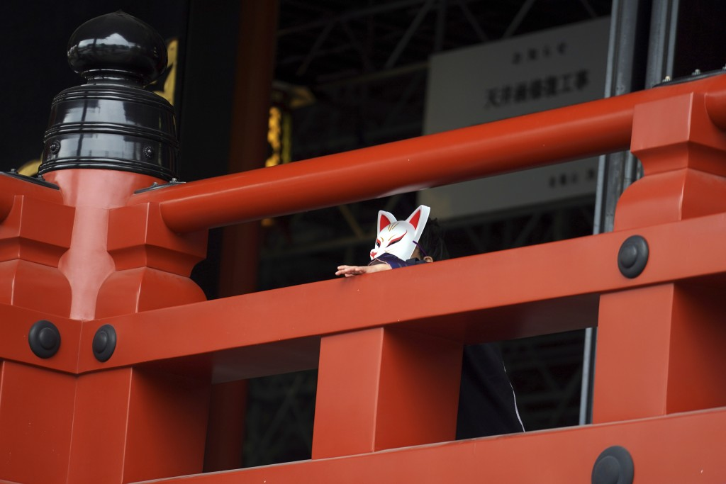 A child wearing traditional mask depicting fox pauses at a shrine Tuesday, Nov. 24, 2020, in Tokyo. The Japanese capital confirmed more than 180 new c...