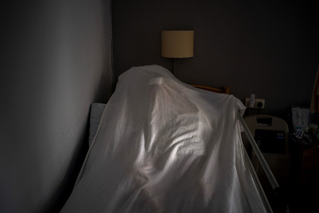 The body of an elderly person who died of COVID-19 is covered with a sheet on a bed in a nursing home in Barcelona, Spain, Friday, Nov. 13, 2020. Like...