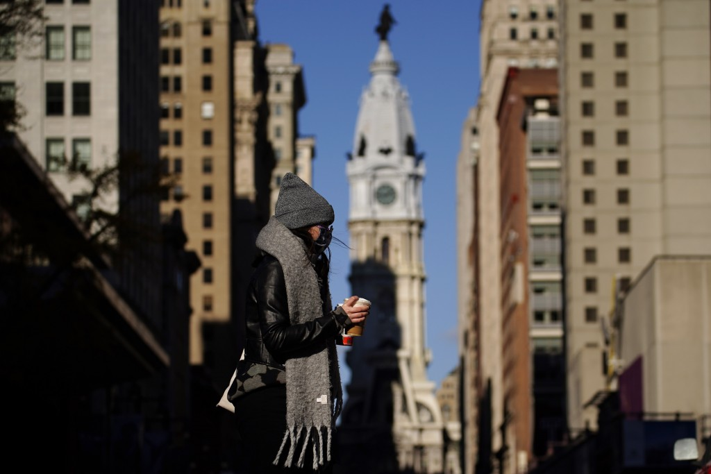 In this Nov. 18, 2020 photo, a person wearing a face mask crosses Broad Street in Philadelphia. As governors and mayors grapple with an out-of-control...