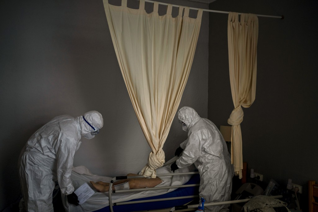 Wearing protective suits to prevent infection, mortuary workers prepare the body of an elderly person who died of COVID-19 before removing it from a n...