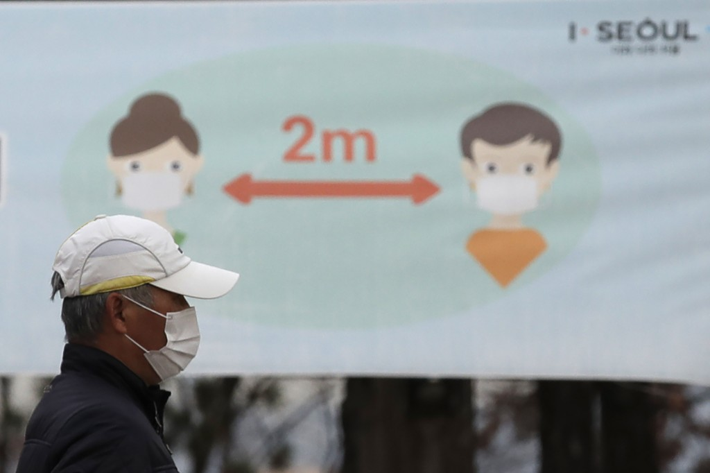 A man wearing a face mask as a precaution against the coronavirus walks past a banner showing social distancing at a park in Seoul, South Korea, Tuesd...