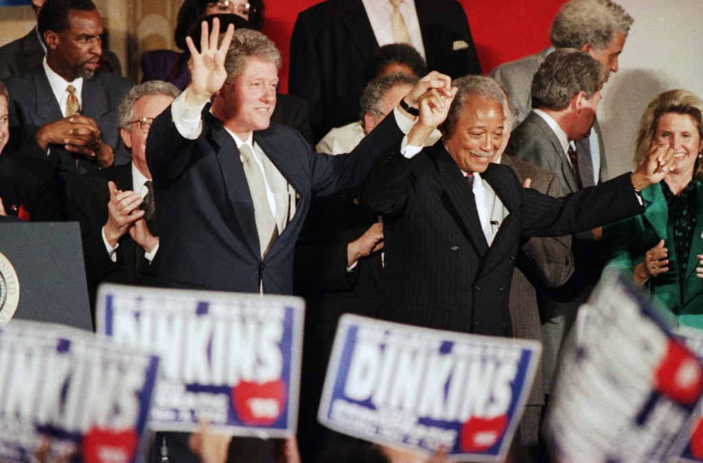 FILE - In this Thursday, Oct. 28, 1993, file photo, President Bill Clinton holds up four fingers signifying four more years as he appears at a Democra...