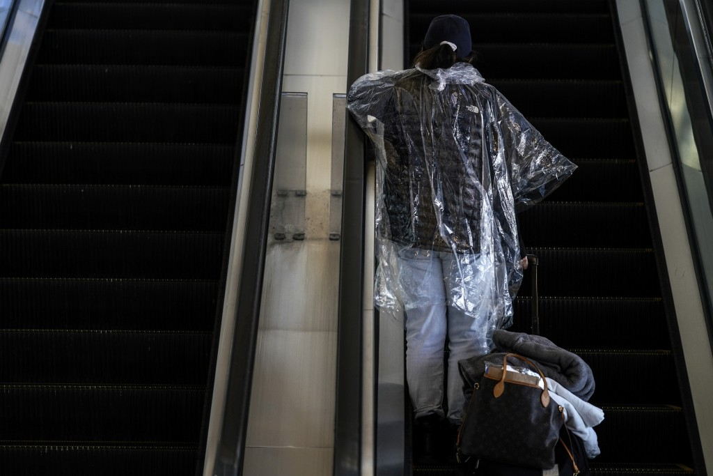 A woman wearing a disposable rain poncho rides an escalator to board her plane at the Los Angeles International Airport in Los Angeles, Monday, Nov. 2...