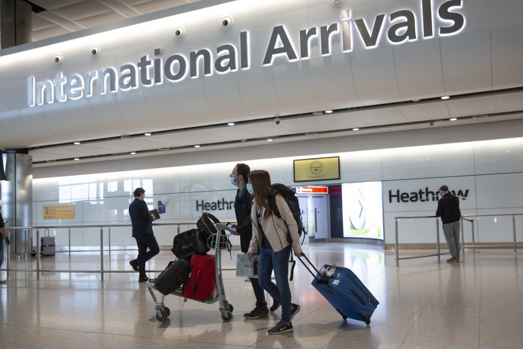 FILE - In this file photo dated Monday, June 8, 2020, passengers wearing face masks arrive at London's Heathrow Airport. The two-week quarantine perio...
