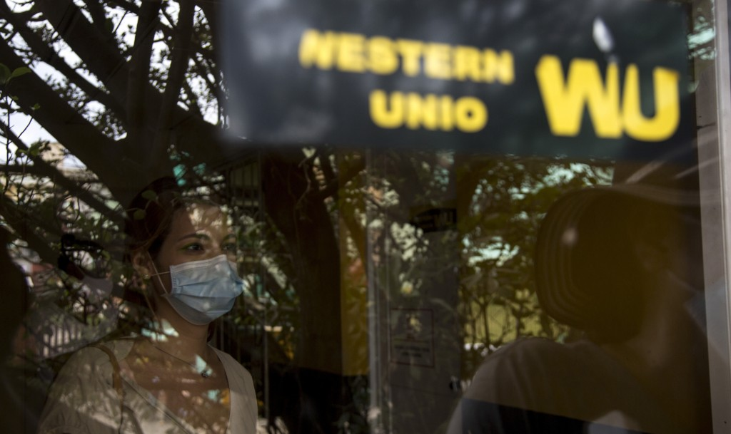 Photographed through a window, a woman waits to collect money at a Western Union office on its last day of business in Havana, Cuba, Monday, Nov. 23, ...