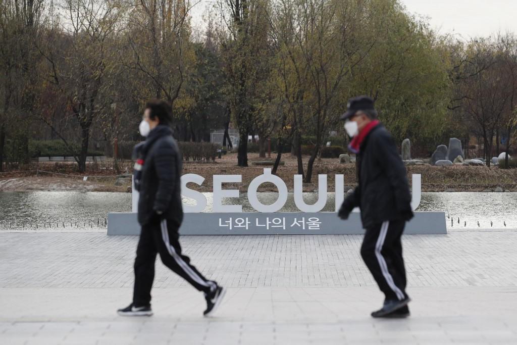 People wearing face masks as a precaution against the coronavirus walk past the display of South Korea's capital Seoul logo at a park in Seoul, South ...