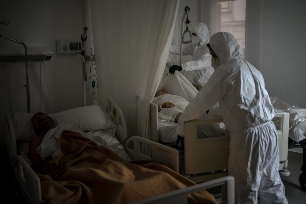 Wearing protective suits to prevent infection, funeral home workers remove the body of an elderly person who died of COVID-19 at a nursing home while ...