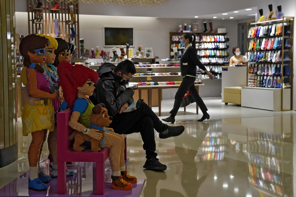 A woman wearing a face mask to help curb the spread of the coronavirus walks by a masked man who sits on a Lego blocks, browsing his smartphone inside...