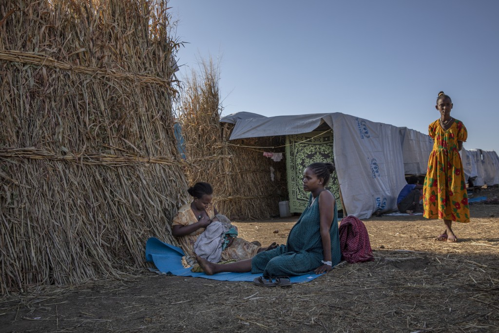 Ethiopian Amhara refugee 8-month pregnant Blaines Alfao Eileen, right, sits with Tigray refugee 25-year-old Lemlem Haylo Rada, holding her one-month o...