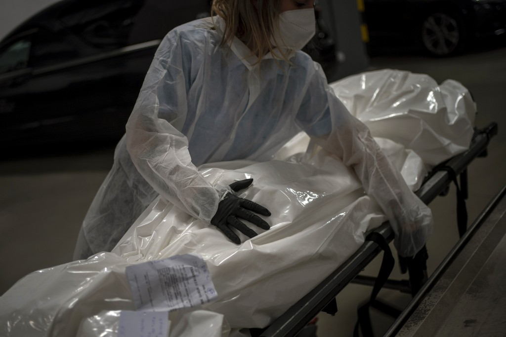 Mortuary worker Marina Gómez handles the body of a person who died of COVID-19 at Mémora morgue in Barcelona, Spain, Monday, Nov. 16, 2020. Gómez and ...