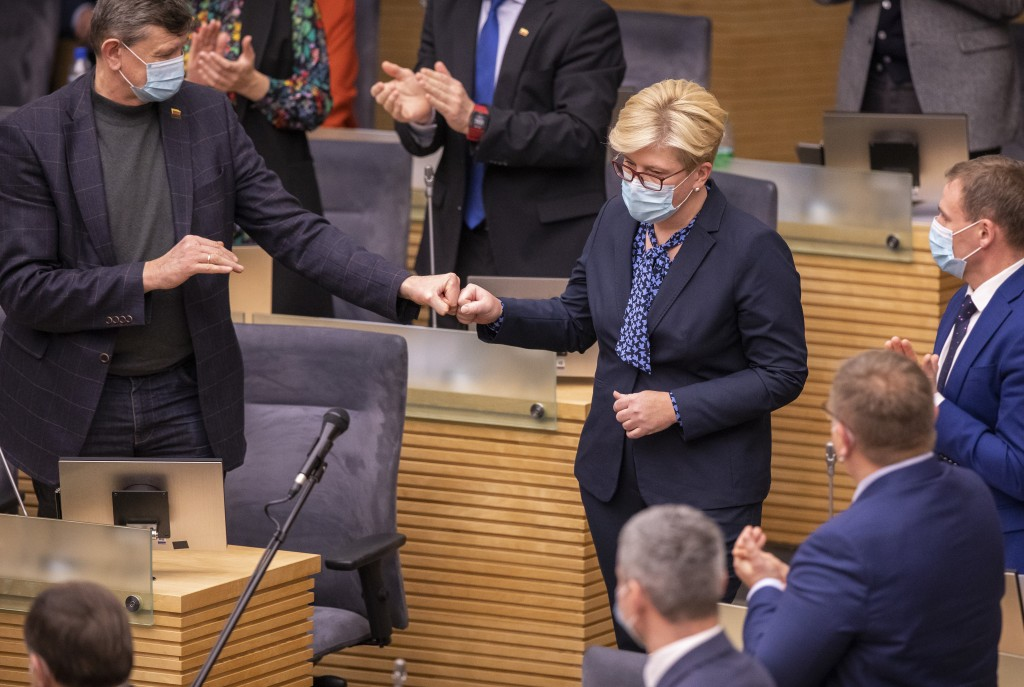 Members of Lithuania's parliament applaud Lithuania's Homeland Union and Lithuanian Christian Democrats party leader Ingrida Simonyte, center, at the ...