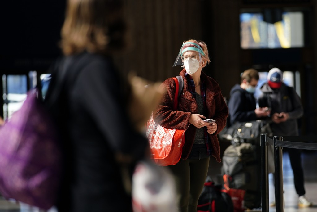 A woman waits in line for a train at the 30th Street Station ahead of the Thanksgiving holiday, Friday, Nov. 20, 2020, in Philadelphia. As governors a...