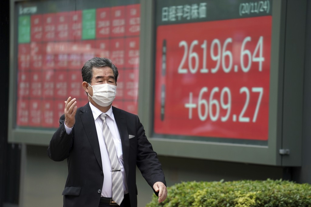 A man wearing a protective face mask to help curb the spread of the coronavirus walks past an electronic stock board showing Japan's Nikkei 225 index ...