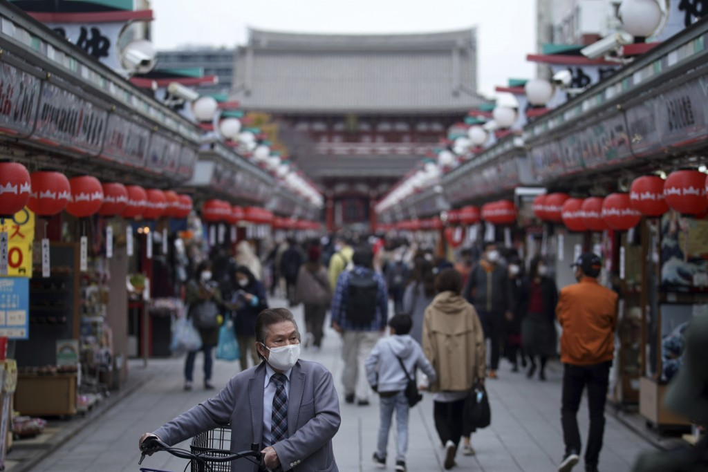 People wearing protective masks to help curb the spread of the coronavirus walk through a shopping arcade at the Asakusa district Tuesday, Nov. 24, 20...