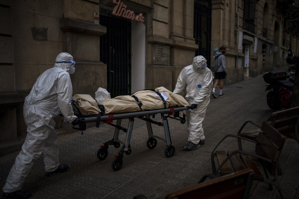 Mortuary workers carry the body of an elderly person who died of COVID-19 after removing it from a nursing home in Barcelona, Spain, Friday, Nov. 13, ...