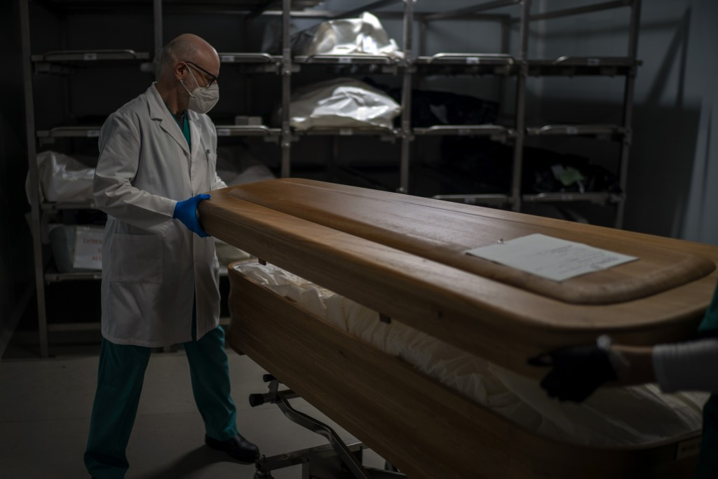 A mortuary worker closes a coffin with body of a COVID-19 victim at Mémora morgue in Barcelona, Spain, Thursday, Nov. 5, 2020. (AP Photo/Emilio Morena...
