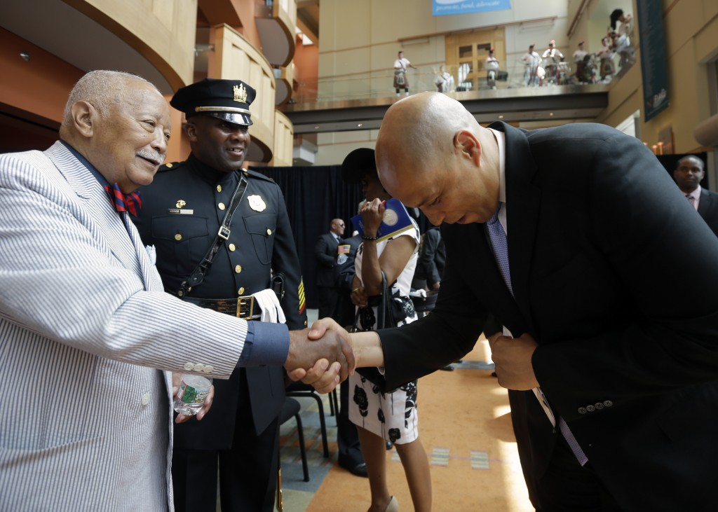 FILE - In this Tuesday, July 1, 2014, file photo, senator and former Newark Mayor Cory Booker bows as he shakes hands with former New York City Mayor ...