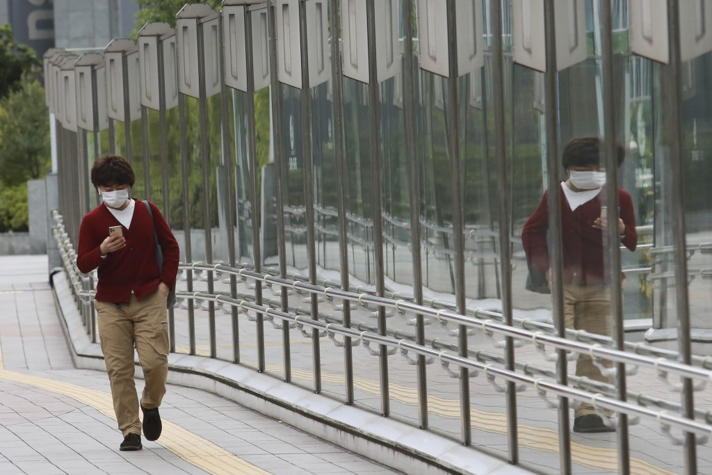 A man wearing a face mask to protect against the spread of the coronavirus walks on a pedestrian overpass in Tokyo, Tuesday, Nov. 24, 2020. (AP Photo/...