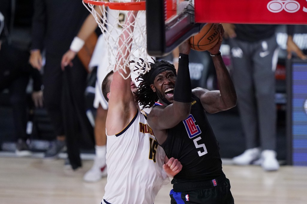 FILE - In this Sept. 15, 2020, file photo, Los Angeles Clippers forward Montrezl Harrell (5) drives to the basket Denver Nuggets center Nikola Jokic (...